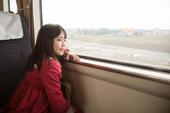 Little asian girl looking through window. Royalty Free Stock Photography