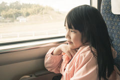 Little asian girl looking through window. She travels on a train Royalty Free Stock Images
