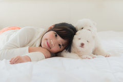 Little asian girl lying with two siberian husky puppies Stock Images