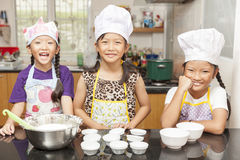 Little asian girl making cotton wool cake. Little asian girl mixing flour to making cotton wool cake in kitchen Royalty Free Stock Images