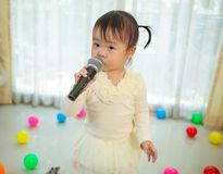 Little asian girl with microphone Royalty Free Stock Image