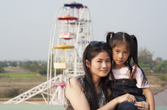 Little Asian girl and mom in amusement park. Royalty Free Stock Image