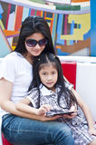 Little asian girl and mom enjoy tablet PC. Royalty Free Stock Photo