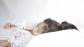 Little Asian girl, mother checking her daughter fever stock footage
