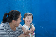Little asian girl and mother play with water hose royalty free stock images