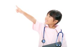Little asian girl in a nurse uniform. Portrait of little asian girl playing nurse pointing, on white background Royalty Free Stock Photography