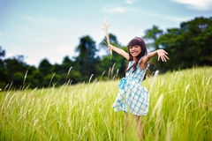 Little asian girl with open arms against green meadow Stock Images