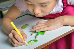 Little Asian girl paint her watercolor picture Royalty Free Stock Photo