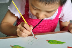 Little Asian girl paints her watercolor picture Royalty Free Stock Photo
