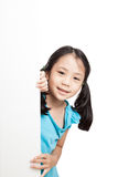 Little asian girl peeking behind a white board. Isolated on white background royalty free stock photos