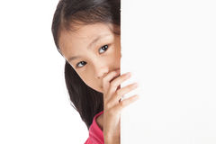Little asian girl peeking behind a white board. Isolated on white background Stock Photography