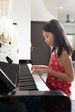 Little Asian girl at piano. Little Asian girl playing piano at home royalty free stock image