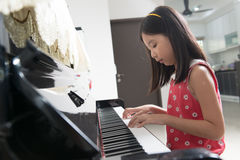 Little Asian girl at piano Royalty Free Stock Photography