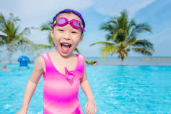 Girl in pink swim suit smiling in swimming pool Stock Photography