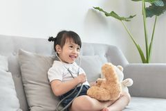 Little asian girl play with baby doll toy.Little asian girl hold stethoscope in hand and check baby doll toy stock photography