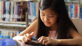 Little Asian girl play a game on smartphone stock video