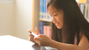 Little Asian girl play a game on smartphone in library stock video