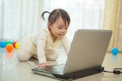 Little asian girl play laptop in home Royalty Free Stock Images