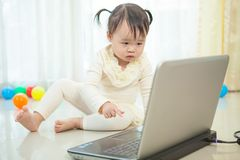 Little asian girl play laptop in home Royalty Free Stock Photos