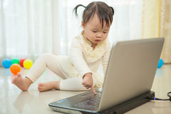 Little asian girl play laptop in home Stock Photo
