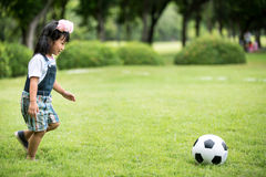 Little asian girl playing football at the park Royalty Free Stock Image