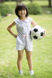 Little asian girl playing football at the park Stock Photos