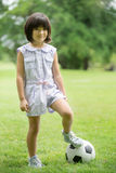 Little asian girl playing football at the park Royalty Free Stock Photos