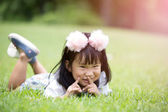 Little asian girl playing on green grass at the park Royalty Free Stock Image
