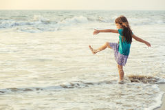 Little asian girl playing and having fun in the sea at sunset Stock Photography