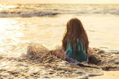 Little asian girl playing and having fun in the sea at sunset Royalty Free Stock Photography