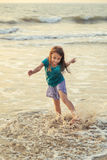Little asian girl playing and having fun in the sea at sunset Royalty Free Stock Photos