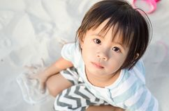 Little asian girl playing with sand stock images