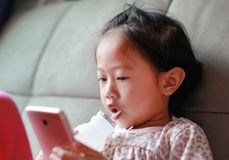 Little Asian girl playing smart phone and drinking milk with straw on sofa at home stock photos