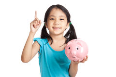 Little asian girl point up with piggy bank Royalty Free Stock Photo