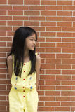 Little Asian girl portrait against brick wall. Royalty Free Stock Image