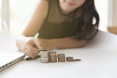 Little asian girl put coin to money stack - money saving educati Royalty Free Stock Images