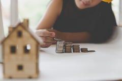 Little asian girl put coin to money stack - money saving educati Stock Photo