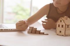 Little asian girl put coin to money stack - money saving educati Royalty Free Stock Image