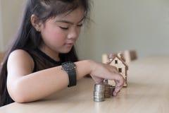 Little asian girl put coin to money stack - money saving educati Royalty Free Stock Photo