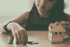 Little asian girl put coin to money stack - money saving educati Stock Image