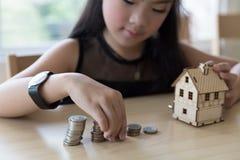 Little asian girl put coin to money stack - money saving educati Stock Photos