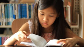 Little Asian girl reading a book. In library, tilt up camera stock video footage