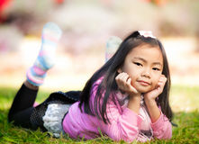 Little asian girl resting on green grass. Little asian girl smile and resting on green grass in cool and royalty free stock photography