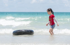Little Asian girl run play waves on the beach Stock Photo