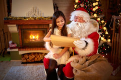 Little Asian girl in Santa Claus lap Royalty Free Stock Photos