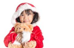 Little Asian girl in santa costume hugging bear doll on christma Stock Photography