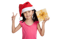 Little asian girl with santa hat and gift box show 2 fingers Stock Photos