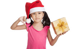 Little asian girl with santa hat and gift box thumbs down Stock Photo