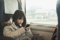 Little asian girl sharing social media in a smart phone Royalty Free Stock Photos