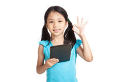 Little asian girl show OK with tablet pc Royalty Free Stock Photo